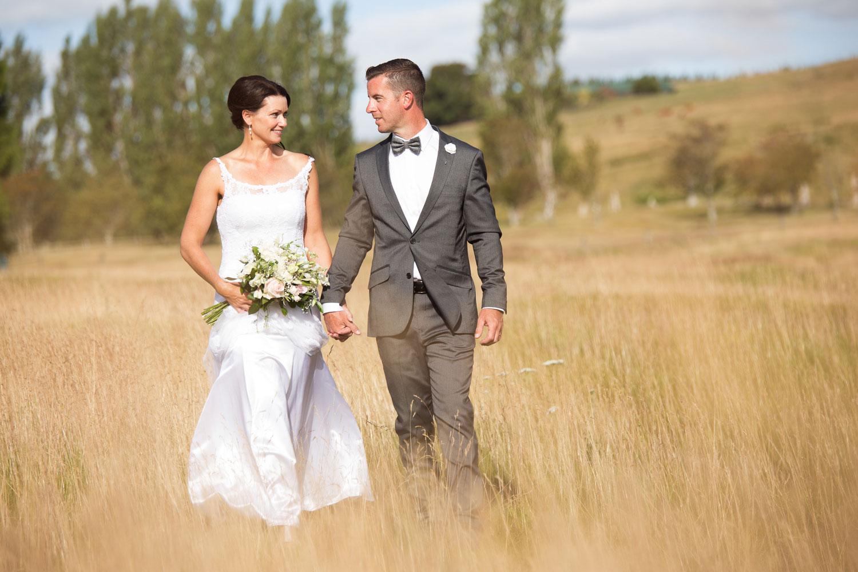 lake taupo wedding photo couple walking in tall grass