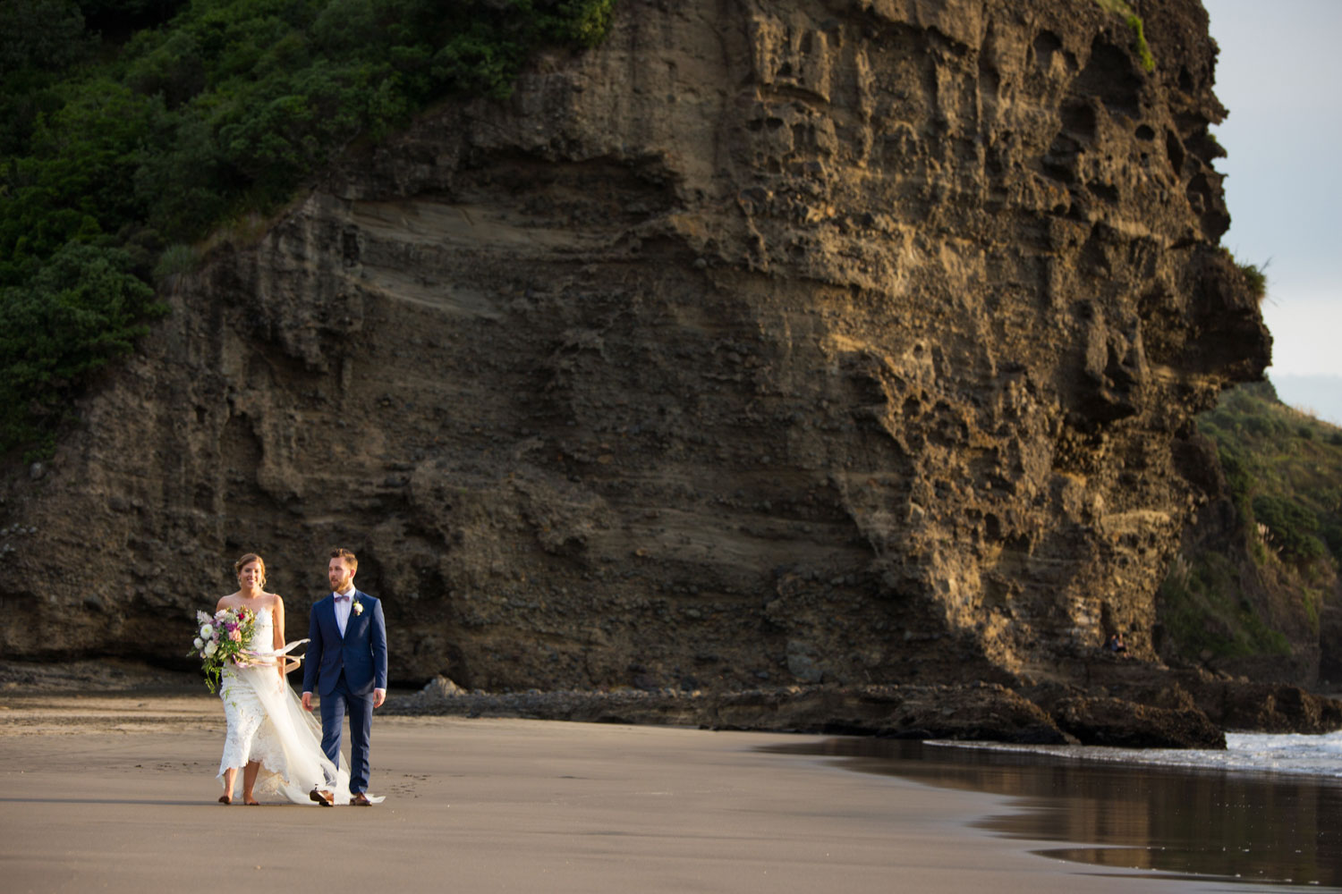 auckland wedding couple walking on piha beach