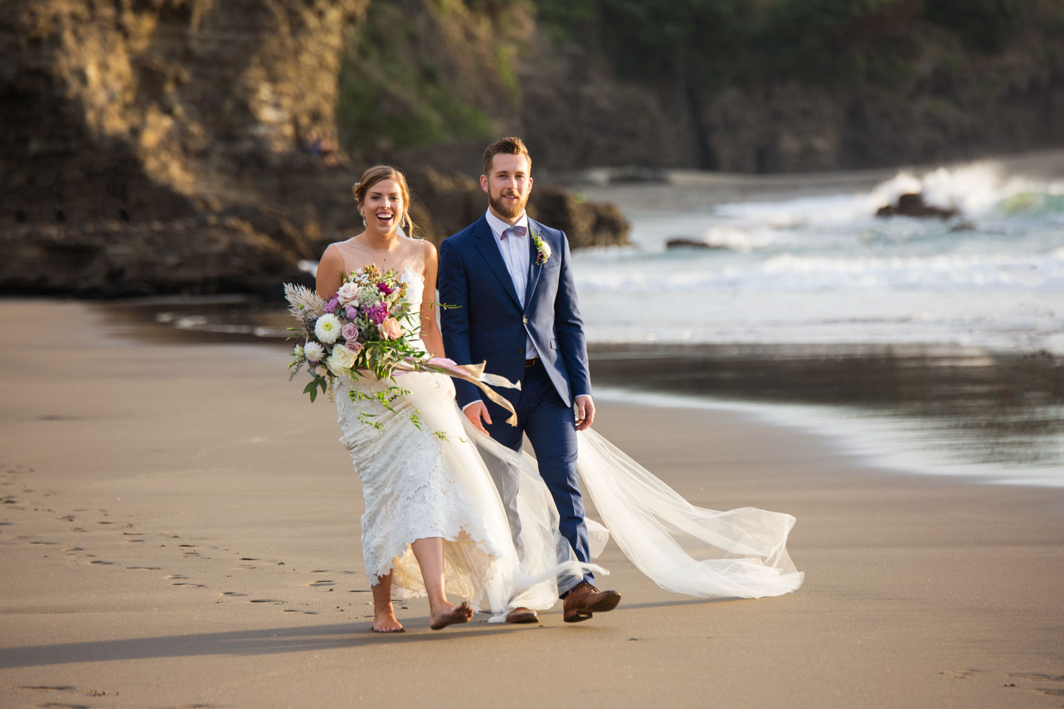 auckland wedding bride and groom walking on piha beach