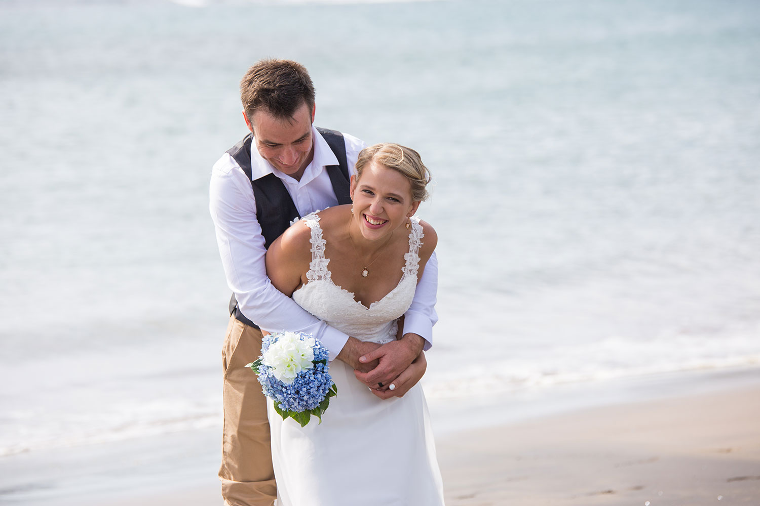 beach wedding groom hugging bride