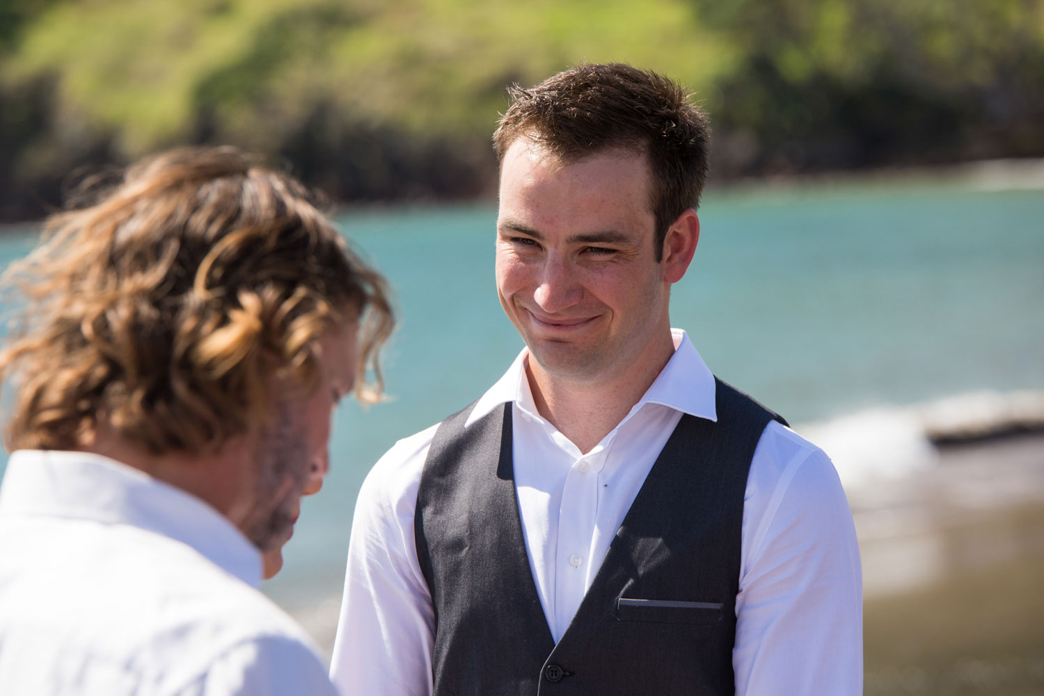 beach wedding groom smiling at bride