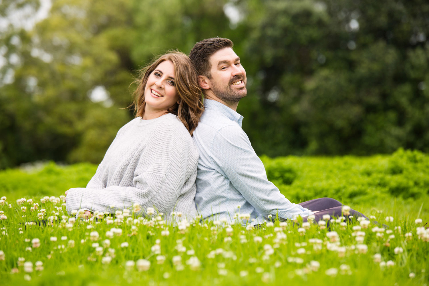 auckland engagement photo western springs couple smiling sitting on flowers