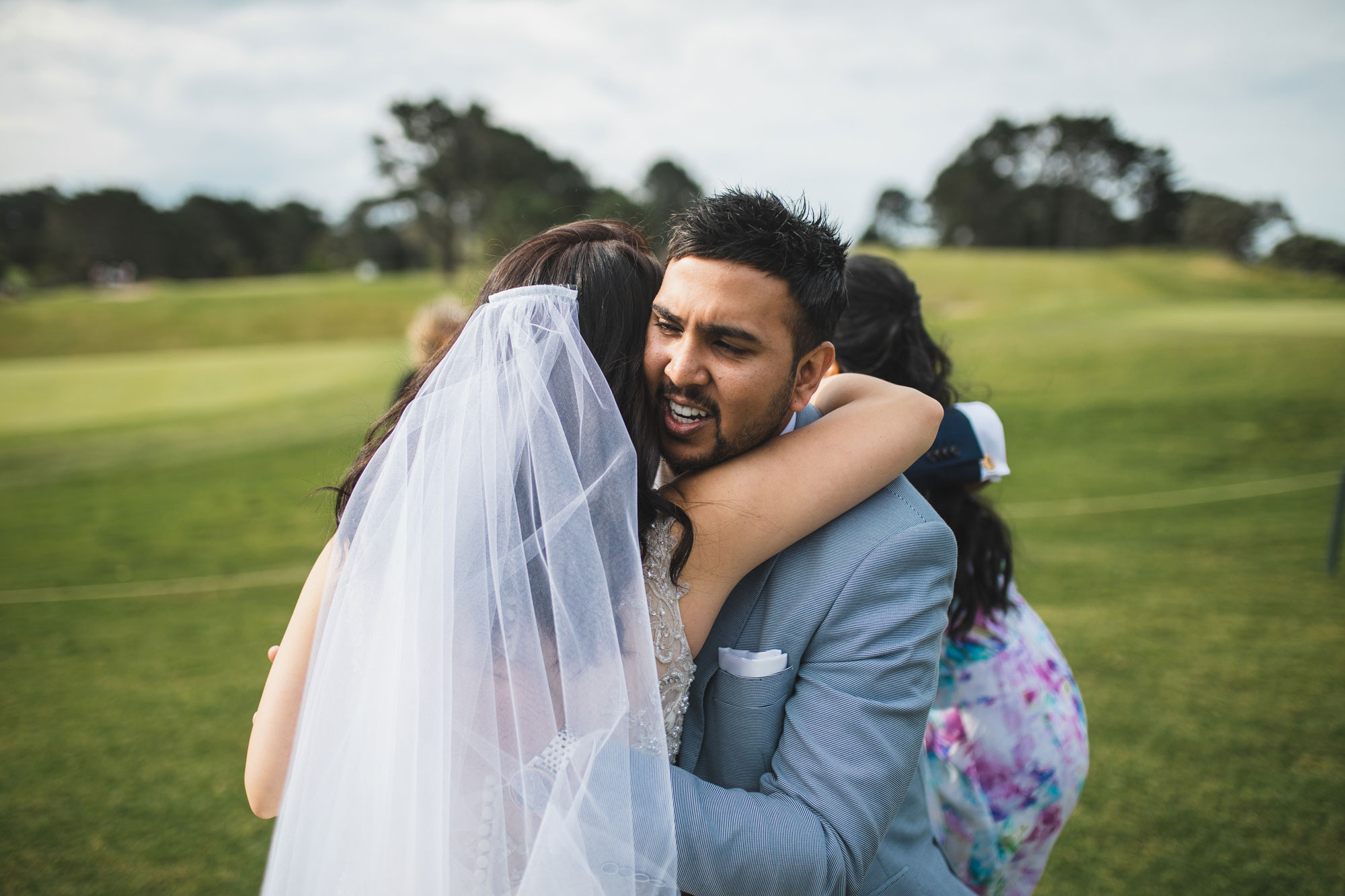 auckland wedding guest hugging bride