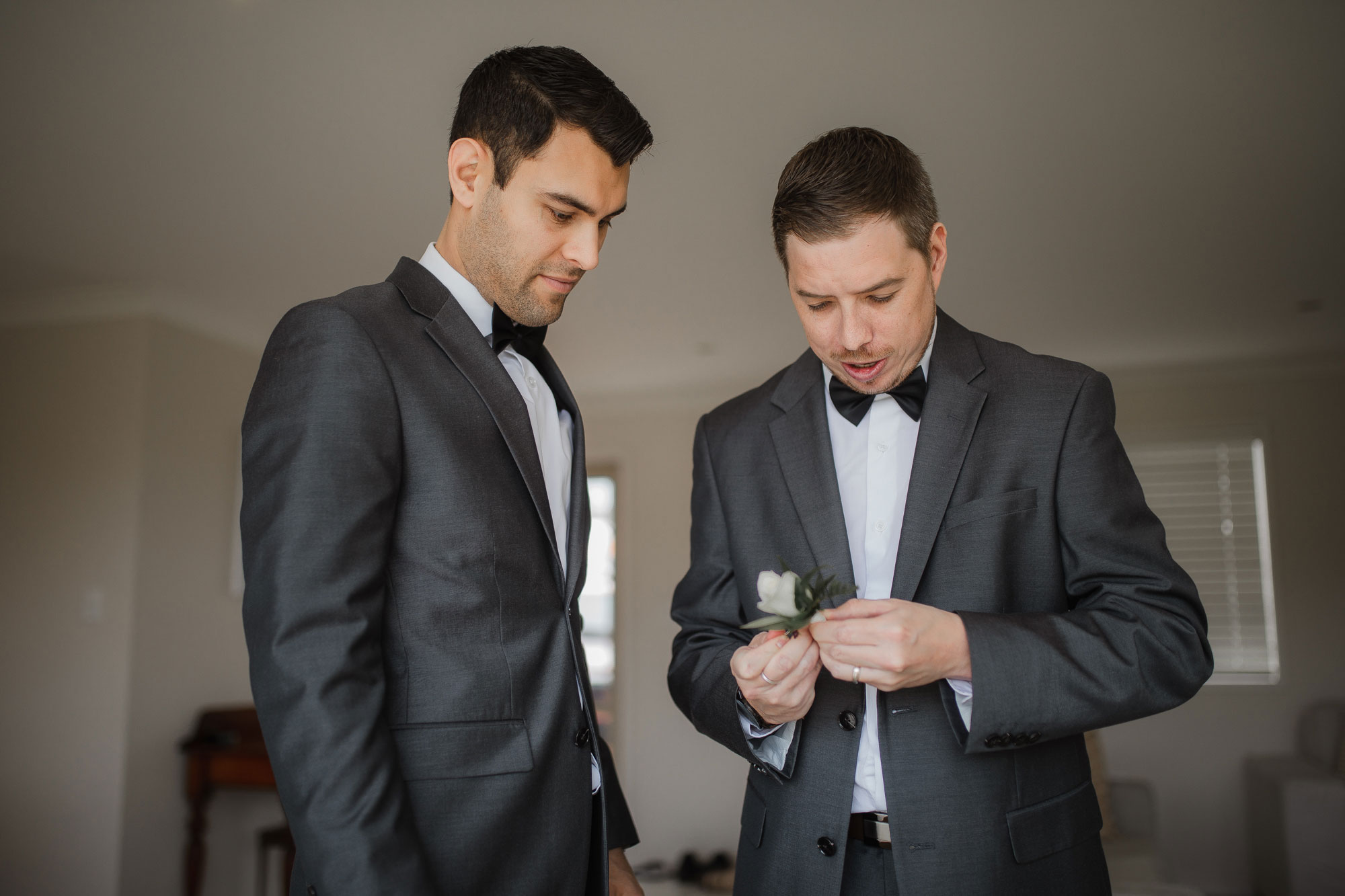 groomsmen putting on buttonhole